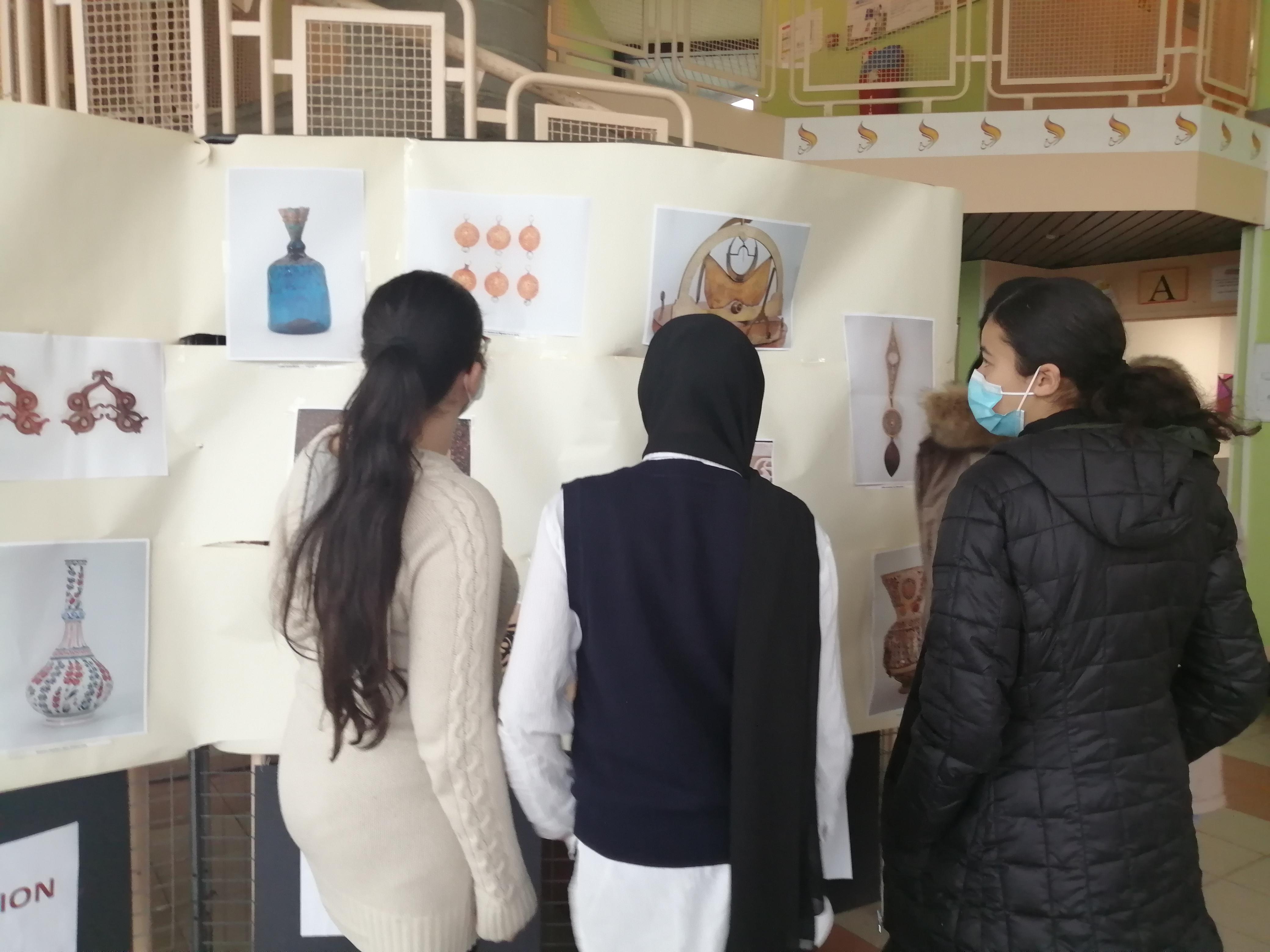 Des collégiennes admirant les pièces artistiques